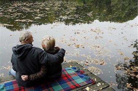 senior couple sitting lakeside Stock Photo - Premium Royalty-Free, Code: 6106-06309240
