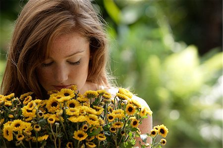 smelling - Young woman smelling big bunch of daisies Stock Photo - Premium Royalty-Free, Code: 6106-06309258
