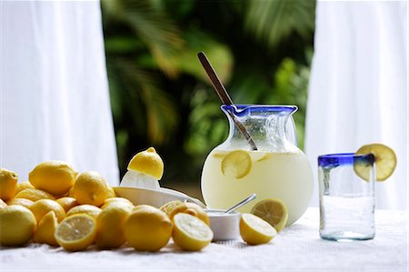 Pitcher of lemonade, glass, lemons on table in kitchen window Stock Photo - Premium Royalty-Free, Code: 6106-06309261