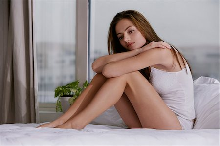 Young woman hugging her knees in bed Stock Photo - Premium Royalty-Free, Code: 6106-06309282