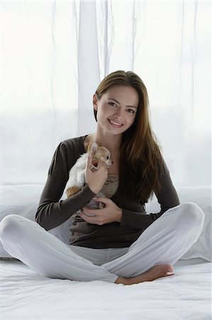 Young woman holding puppy Stock Photo - Premium Royalty-Free, Code: 6106-06309366