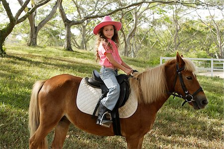 Young girl riding pony Stock Photo - Premium Royalty-Free, Code: 6106-06309625