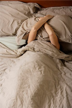 woman in bed covering her head with a pillow Stock Photo - Premium Royalty-Free, Code: 6106-06309959