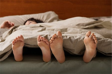 Feet of man and woman in bed Stock Photo - Premium Royalty-Free, Code: 6106-06309968
