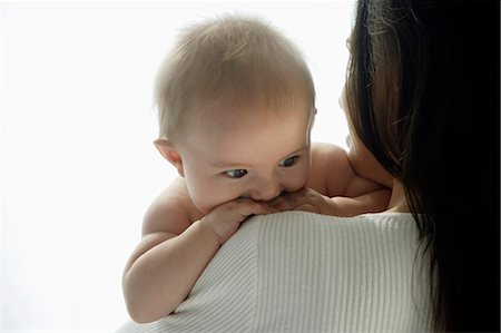 mother holding baby looking over her shoulder Stock Photo - Premium Royalty-Free, Code: 6106-06309992