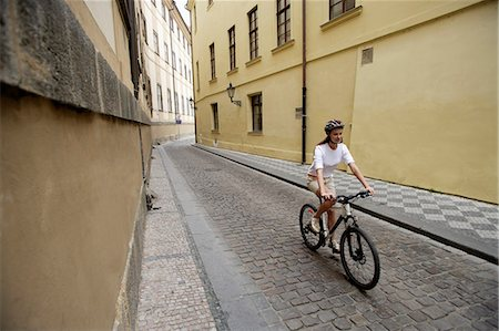 young woman riding bicycle down cobblestone street Stock Photo - Premium Royalty-Free, Code: 6106-06310126
