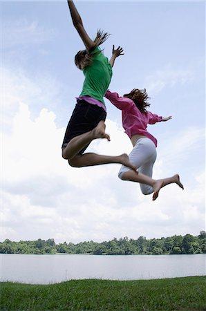 Teen girls jumping by lake Stock Photo - Premium Royalty-Free, Code: 6106-06310683
