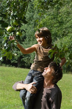 family apple orchard - father holding son up to pick apple from tree Stock Photo - Premium Royalty-Free, Code: 6106-06311290