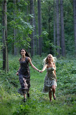 Young women running through forest Stock Photo - Premium Royalty-Free, Code: 6106-06311200