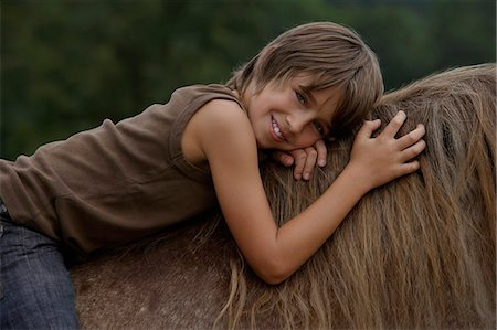 preteen  smile  one  alone - boy on horseback Stock Photo - Premium Royalty-Free, Code: 6106-06311306