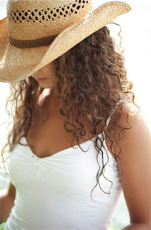 Woman wearing straw hat, looking down Stock Photo - Premium Royalty-Free, Code: 6106-06311450