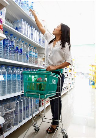 Woman reaching for product in supermarket Stock Photo - Premium Royalty-Free, Code: 6106-06311472