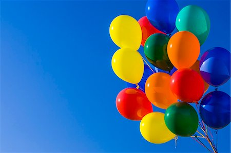 Colorful balloons against blue sky Stock Photo - Premium Royalty-Free, Code: 6106-06334934