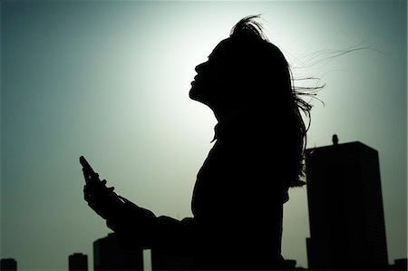 silhouettes - businesswoman with mobile phone Stock Photo - Premium Royalty-Free, Code: 6106-06335069