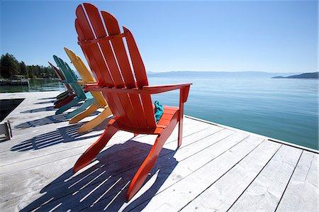 Row of adirondak chairs on dock by scenic lake Stock Photo - Premium Royalty-Free, Code: 6106-06335219