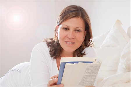 Woman lying on bed, reading a book Stock Photo - Premium Royalty-Free, Code: 6106-06495871