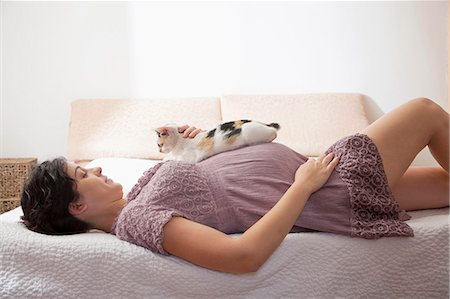 Pregnant woman in bed with her cat Stock Photo - Premium Royalty-Free, Code: 6106-06495912
