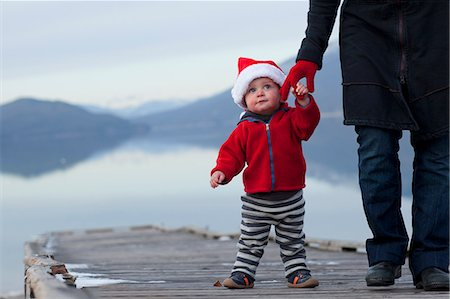 Toddler wears Santa hat and holds mothers hand Stock Photo - Premium Royalty-Free, Code: 6106-06496175