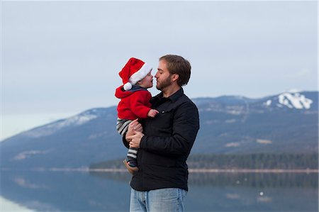 Toddler wears Santa hat and speaks to father Stock Photo - Premium Royalty-Free, Code: 6106-06496176