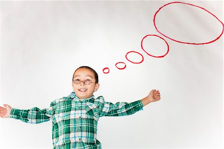 A young boy with thought bubbles around him. Stock Photo - Premium Royalty-Free, Code: 6106-06496443