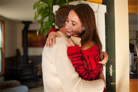 Woman happily embraces partner with gift Stock Photo - Premium Royalty-Free, Code: 6106-06496713