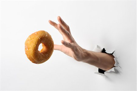 Hand trying to take a donut Stock Photo - Premium Royalty-Free, Code: 6106-06401783