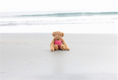 Teddy bear sitting on the beach Stock Photo - Premium Royalty-Free, Code: 6106-06402249