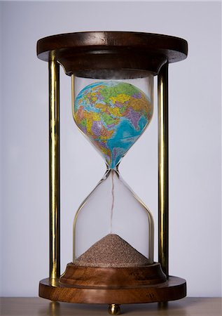 Globe turning sand in a hourglass Stock Photo - Premium Royalty-Free, Code: 6106-06434829