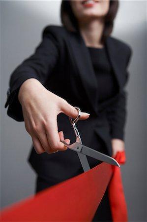 Studio shot of businesswoman cutting red ribbon, m Stock Photo - Premium Royalty-Free, Code: 6106-06535472