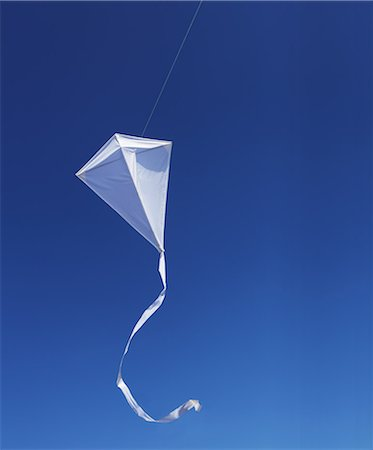 White kite against blue sky. Stock Photo - Premium Royalty-Free, Code: 6106-06535707