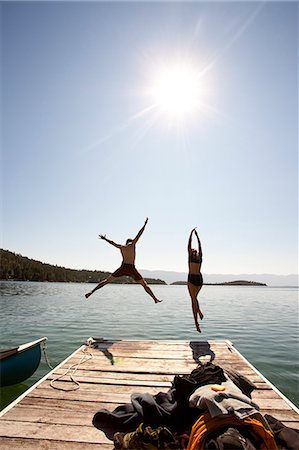 Man and woman jumping off end of dock. Stock Photo - Premium Royalty-Free, Code: 6106-06535889