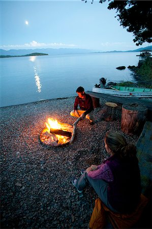 Man and woman by campfire at night on lake shore. Stock Photo - Premium Royalty-Free, Code: 6106-06535892