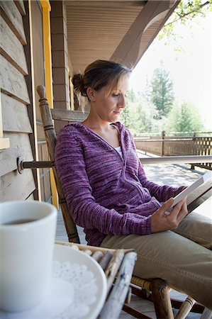 Woman reading book on poarch. Stock Photo - Premium Royalty-Free, Code: 6106-06536024