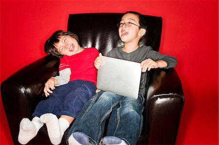 red chair - Two brothers using a tablet device inside. Stock Photo - Premium Royalty-Free, Code: 6106-06536437