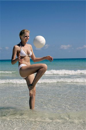 woman playing on seaside with ball Stock Photo - Premium Royalty-Free, Code: 6106-06614294