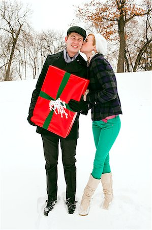 A young couple standing outside with a gift. Stock Photo - Premium Royalty-Free, Code: 6106-06614751