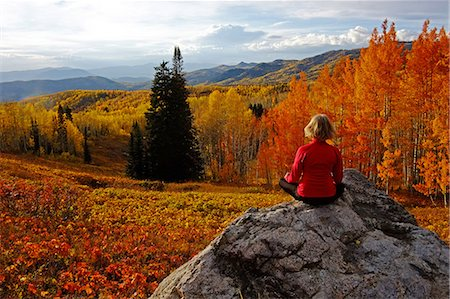 Woman siting on rock in fall colors Stock Photo - Premium Royalty-Free, Code: 6106-06614884