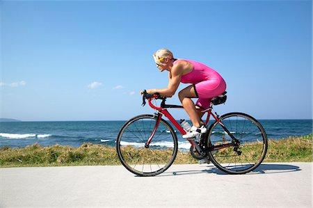 Professional Cyclist riding along Australian Beach Stock Photo - Premium Royalty-Free, Code: 6106-06831186