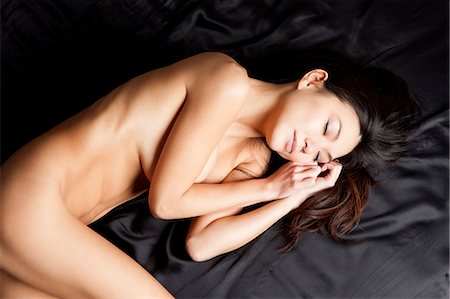 sleeping nude - Naked Woman Sleeping On Bed Stock Photo - Premium Royalty-Free, Code: 6106-06831798