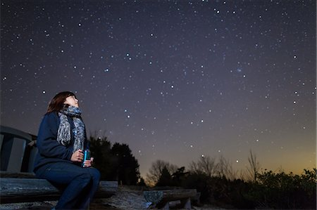 people sitting on bench - A woman sitting on a bench looking up at stars Stock Photo - Premium Royalty-Free, Code: 6106-06832014