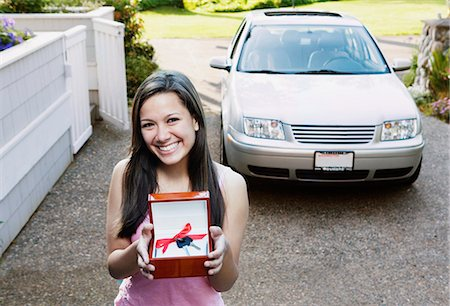 Teenage girl (14-16) standing in driveway, holding car keys with bow Stock Photo - Premium Royalty-Free, Code: 6106-06977899