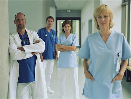 Doctors and nurses standing in hospital corridor, portrait Stock Photo - Premium Royalty-Free, Code: 6106-06978136