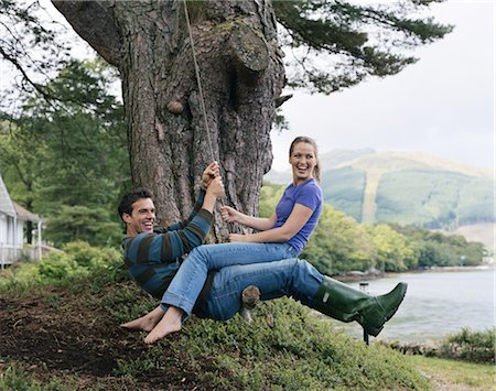 Woman sitting on man's lap on swing, smiling Stock Photo - Premium Royalty-Free, Code: 6106-06978288