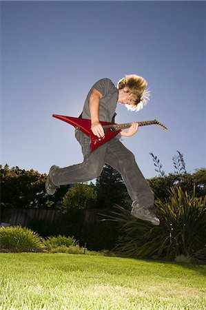 Teenage boy (12-14) playing electric guitar in yard, jumping in midair Stock Photo - Premium Royalty-Free, Code: 6106-06979087