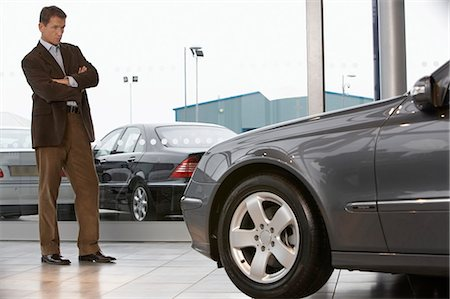 Businessman standing in front of car in showroom with arms folded Stock Photo - Premium Royalty-Free, Code: 6106-06979290