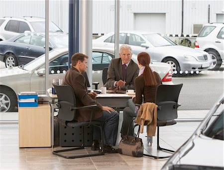 Mature salesman sitting at desk with couple in car showroom Stock Photo - Premium Royalty-Free, Code: 6106-06979294