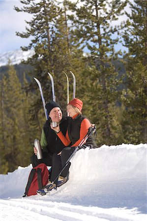 Senior man and woman with cross-country skis drinking beverage in snow Stock Photo - Premium Royalty-Free, Code: 6106-06979801