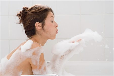 Young woman in bubbles bath, blowing suds from hands, side view Stock Photo - Premium Royalty-Free, Code: 6106-06980579