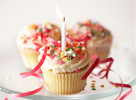 Cupcakes with icing, sprinkles and candle, elevated view Stock Photo - Premium Royalty-Free, Code: 6106-06981158