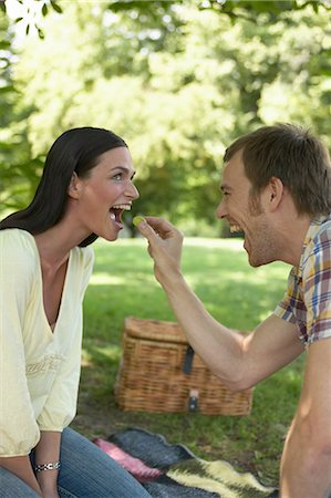Couple having picnic in park, man feeding woman grape, smiling Stock Photo - Premium Royalty-Free, Code: 6106-06981665